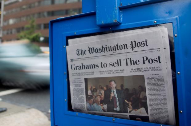The news that the owners of the Washington Post are to sell the newspaper to billionaire Jeff Bezos is displayed on the front page of the newspaper in Washington, D.C., U.S., on Tuesday, Aug. 6, 2013. Amazon.com Inc. Chief Executive Officer Bezos agreed to buy the Washington Post for $250 million, betting that he can apply his success in e-commerce to the struggling newspaper industry (Andrew Harrer/Bloomberg)