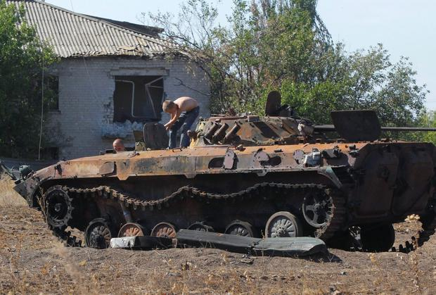 People loosen parts from a burned-out Ukrainian armored personnel carrier in the village of Hrabske, eastern Ukraine, Sunday, Aug. 31, 2014. The fight for Ilovaisk and surrounding areas, including the village of Hrabske, between Ukrainian government troops and pro-Russian separatist fighters was bitter and lasted the best part of a month. (AP Photo/Sergei Grits)