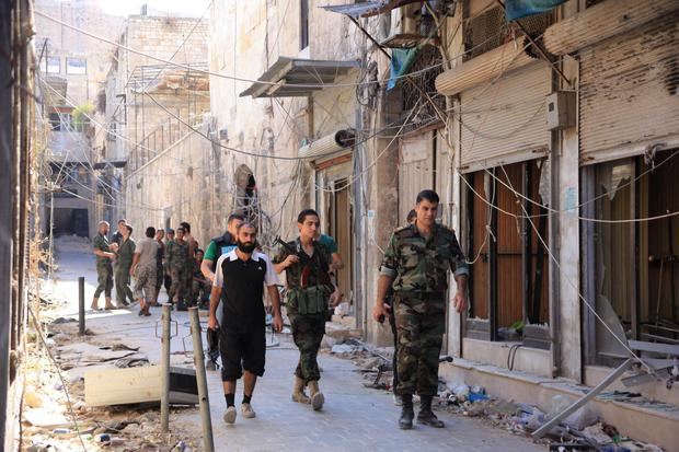 Forces loyal to Syria's President Bashar al-Assad walk in Old Aleppo, after claiming to have advanced in the area. REUTERS/George Ourfalian