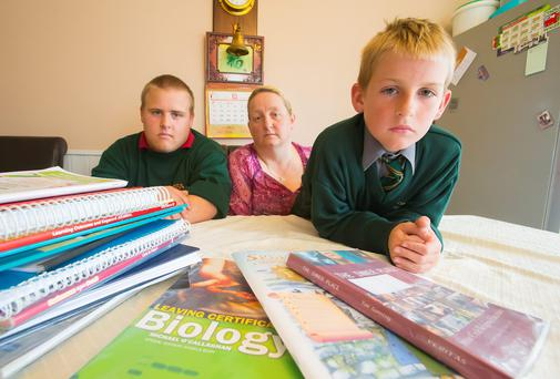 Linda O'Shea from Waterford City with her sons, Daniel, 5th year St. Paul's and Jack, 6th class, Scoil Lorcáin with some of their school books. Picture: Patrick Browne