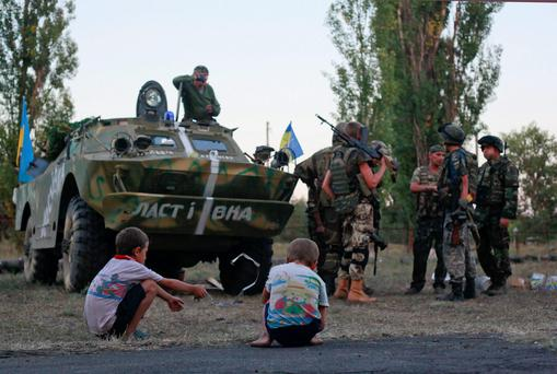 Children watch as the Ukrainian soldiers talk to each other in the small town of Shchastya in eastern Ukraine. A Ukrainian military official says the bodies of 87 soldiers have been retrieved from southeastern Ukraine.