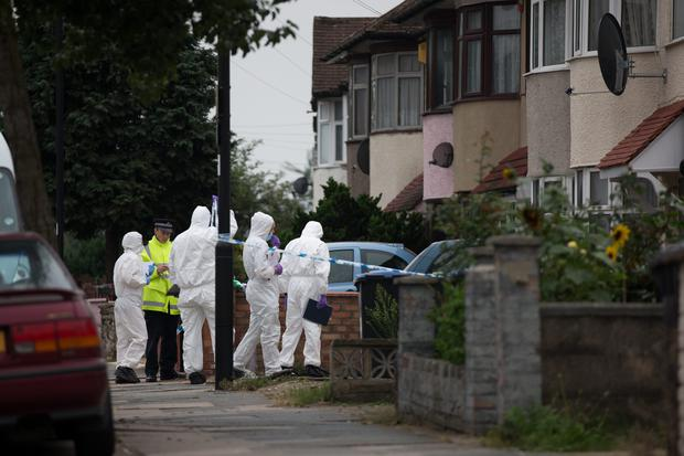 Forensic investigators examine a property in London where a woman was beheaded