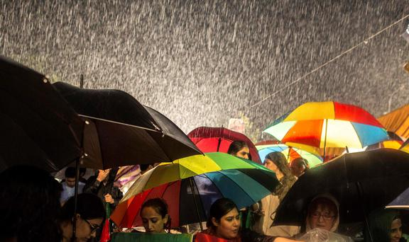 Anti-government protesters wait for a speech by their leader Imran Khan, Chairman of the Pakistan Tehreek-e-Insaf (PTI) political party, during heavy rain in front of the Parliament house in the Red Zone during the Revolution March in Islamabad