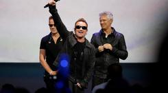 Bono gestures to the audience after performing at an Apple event at the Flint Center in Cupertino, California