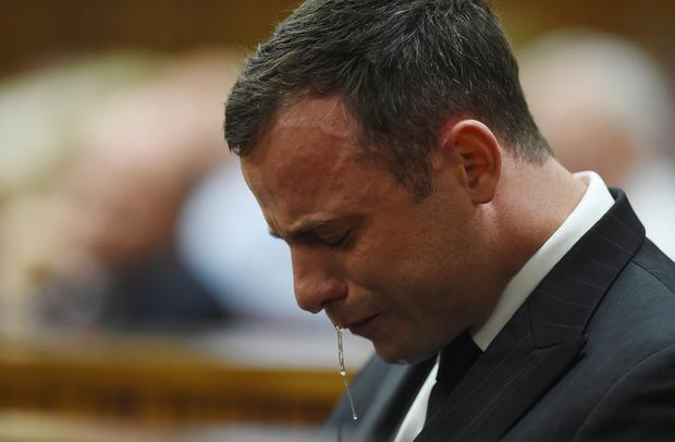Oscar Pistorius cries in the dock in Pretoria, South Africa, Thursday Sept. 11, 2014 as Judge Thokozile Masipa reads notes as she delivers her verdict in Pistorius' murder trial. The South African judge in Oscar Pistorius murder trial said Thursday that prosecutors have not proved beyond a reasonable doubt that the double-amputee Olympic athlete is guilty of premeditated murder. (AP Photo/Phil Magakoe, Pool)