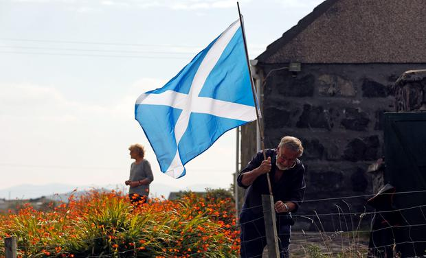 A man erects a Scottish Saltire in the garden of his cottage on the Isle of Lewis in the Outer Hebrides yesterday. Photo credit: REUTERS/Cathal McNaughton