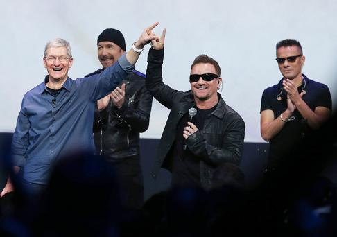 Bono and Apple boss Tim Cook do their ET finger touch as the Edge and Larry Mullen applaud.