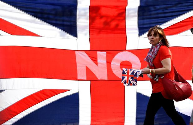 A loyalist marches past a Union flag during a pro-Union rally in Edinburgh, Scotland.REUTERS/Dylan Martinez