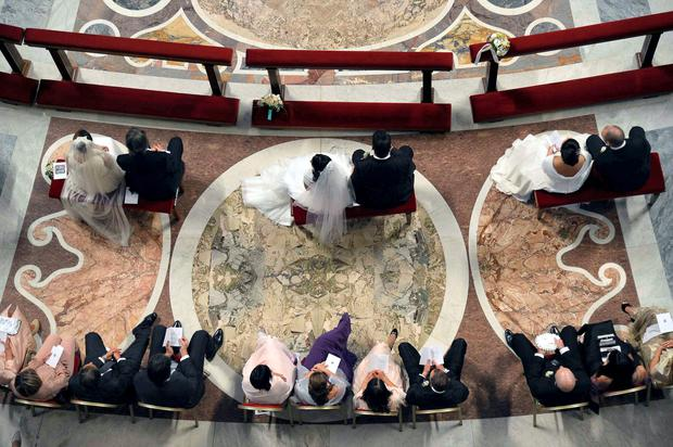 Pope Francis (not pictured) officiates a mass at the wedding of 20 couples in St.Peter's Basilica at the Vatican, September 14, 2014.