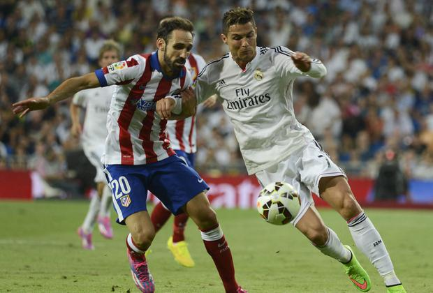 Cristiano Ronaldo vies for the ball with Athletico's Juanfran. File Photo: Evrim Aydin/Anadolu Agency/Getty Images