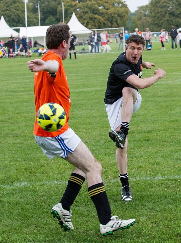 Phoenix Park: Sport Against Racism Ireland (SARI) organised a Sari All-Stars v Love/Hate cast football match. Aiden Gillen shoots on goal with Aodhan O Riordhan TD Minister of State defending.