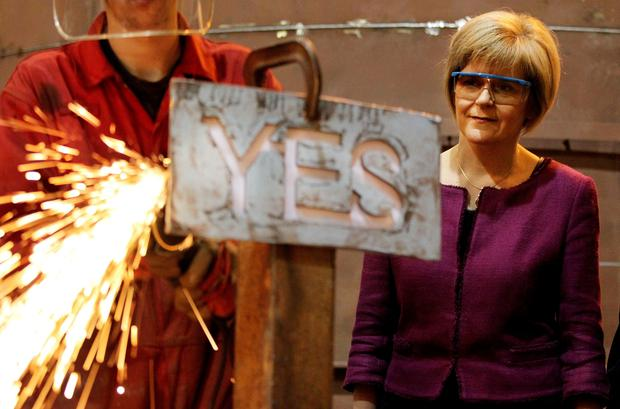 Deputy First Minister Nicola Sturgeon watching apprentice Craig McKee manufacturing a steel 'Yes' sign at Steel Engineering in Renfrew, Scotland ahead of the Scottish independence referendum on Thursday (Lynne Cameron/PA Wire)