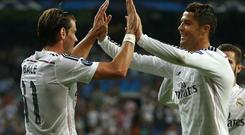 Real Madrid's Gareth Bale celebrates with teammate Cristiano Ronaldo scoring his side's second goal during the Champions League Group B soccer match between Real Madrid and Basel at the Santiago Bernabeu stadium