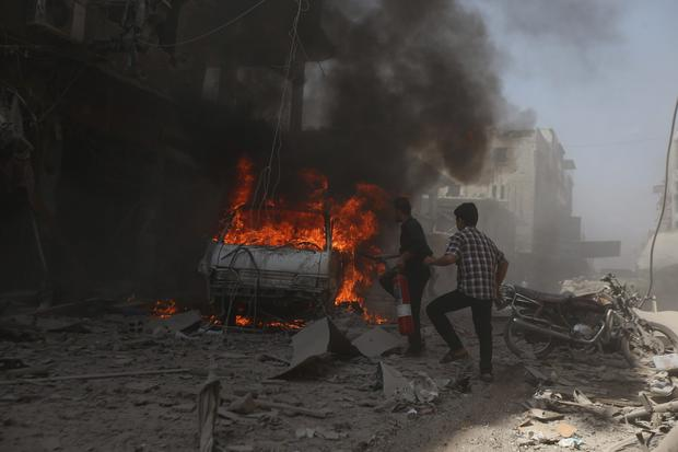 Residents try to put out a fire at a site after what activists said were two air strikes by forces of Syria's President Bashar al-Assad on a market in central Douma, eastern al-Ghouta, near Damascus. It was reported yesterday that the death toll from government airstrikes in the central city of Talbiseh climbed to nearly 50. Photo credit: REUTERS/Bassam Khabieh