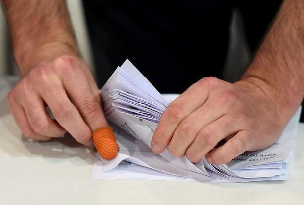 A man counts ballots at a counting centre in Aberdeen, Scotland