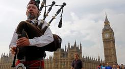 Piper Anton Doherty plays to passers-by in front of the Houses of Parliament on Westminster Bridge in London September 18, 2014.