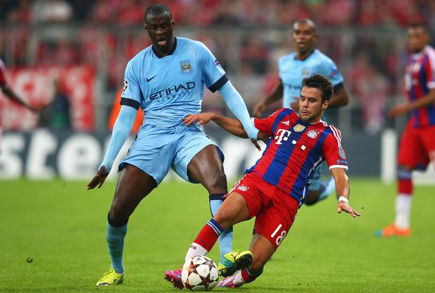 Yaya Toure is tackled by Munich's Juan Bernat. Photo credit: Alex Grimm/Bongarts/Getty Images