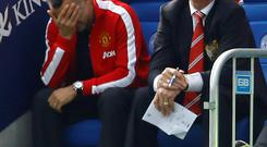 Manchester United manager Louis Van Gaal (R) and his assistant Ryan Giggs react during their English Premier League soccer match against Leicester City