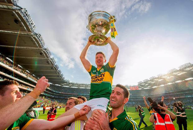 Kieran O'Leary, joint captain of Kerry, is lifted shoulder high by Bryan Sheehan. Picture credit: David Maher / SPORTSFILE