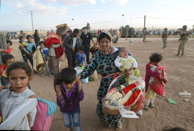Syrian refugees gather at the border in Suruc, Turkey. (AP Photo)
