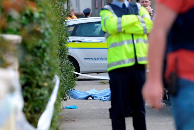 General view Gardai on scene with body on ground. Clonard Street, Balbriggan, Dublin