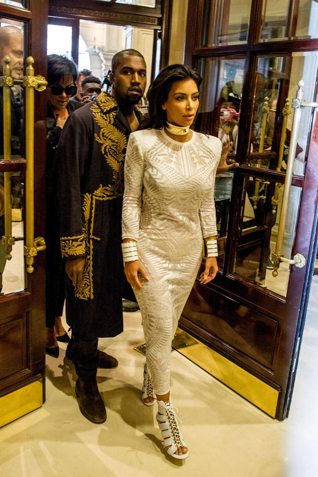 Kim Kardashian and her husband U.S rap artist Kanye West arrive at the Balmain Spring/Summer 2015 ready-to-wear fashion collection, in Paris, France. (AP Photo/Zacharie Scheurer)