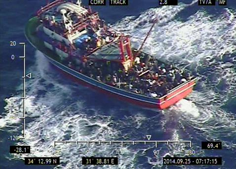 In this photo provided the Cypriot Defense Ministry, a small vessel loaded with 353 people who are believed to be refugees fleeing Syria lies around 50 nautical miles southwest of Cyprus' coast on Thursday, Sept. 25, 2014. (AP Photo/Cypriot Defense Ministry, HO)