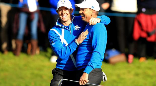Europe's Sergio Garcia celebrates after chipping in from a bunker with playing partner Rory McIlroy during the fourballs this morning