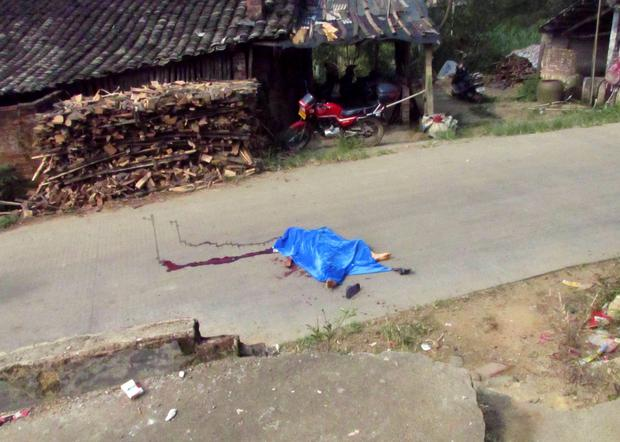 The body of a child is pictured on a road leading to a primary school in Lingshan county, Guangxi Zhuang Autonomous region, September 26, 2014. REUTERS/Stringer