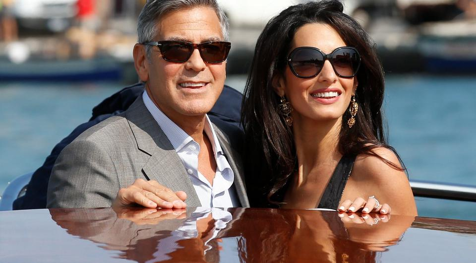 George Clooney, left, and Amal Alamuddin arrive in Venice, Italy, Friday, Sept. 26, 2014. Clooney, 53, and Alamuddin, 36, are expected to get married this weekend in Venice, one of the worlds most romantic settings. (AP Photo/Luca Bruno)