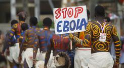 Actors parade on a street after performing at Anono school, during an awareness campaign against Ebola in Abidjan. The tag on one of the actors read: 'Red card to Ebola'. Reuters