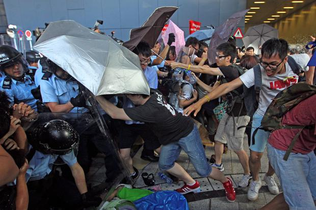 Riot policemen scuffle with protesters after young pro-democracy activists forced their way into Hong Kong government headquarters during a demonstration in Hong Kong, early Saturday