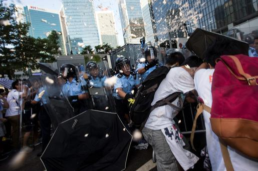 Riot police target pro-democracy students with pepper spray after hundreds of protesters stormed into a restricted area at the government headquarters, after a rally ahead of the October 1