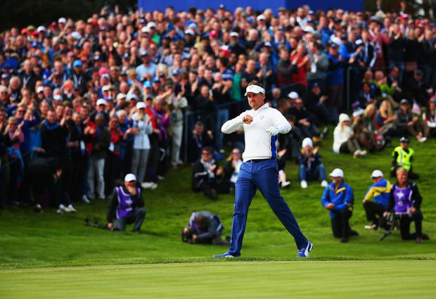Ian Poulter of Europe celebrates chipping in on the 15th hole during the morning fourballs