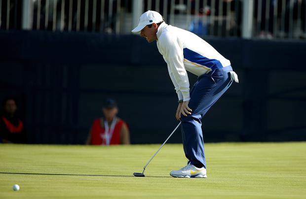 Rory McIlroy reacts to a missed putt on the 13th green during the morning fourballs