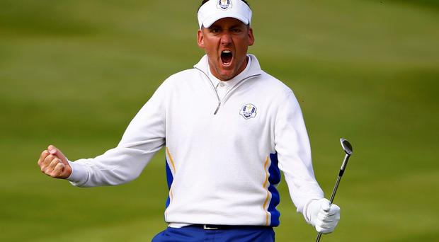 European Ryder Cup player Ian Poulter reacts after chipping into the hole on the 15th green