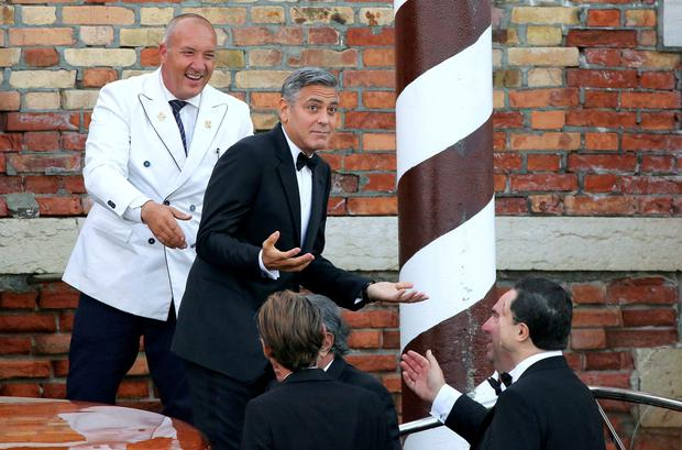 U.S. actor George Clooney (top 2nd L) gestures as he leaves by taxi boat to travel to the venue of a gala dinner ahead of his official wedding ceremony in Venice September 27, 2014.