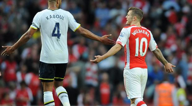 Tottenham Hotspur's Younes Kaboul (left) and Arsenal's Jack Wilshere exchange words during the Barclays Premier League match at the Emirates Stadium, London