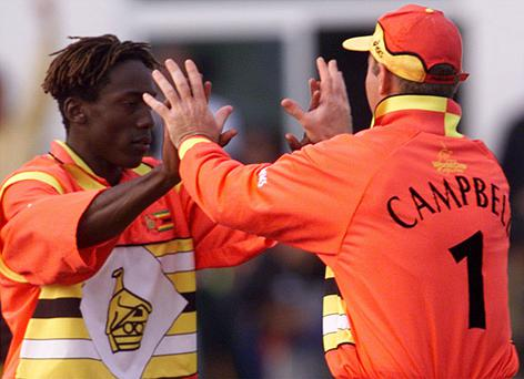 Zimbabwe's Henry Olonga (L) is congratulated by Zimbabwe captain Alistair Campbell during a match against India in 1999. Photo: Paul Hackett/Reuters.