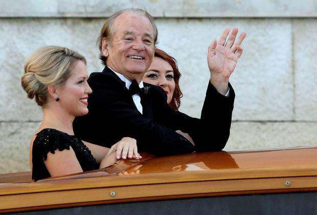 U.S. actor Bill Murray waves as he boards a taxi boat transporting guests to the venue of a gala dinner ahead of the official wedding ceremony of U.S. actor George Clooney