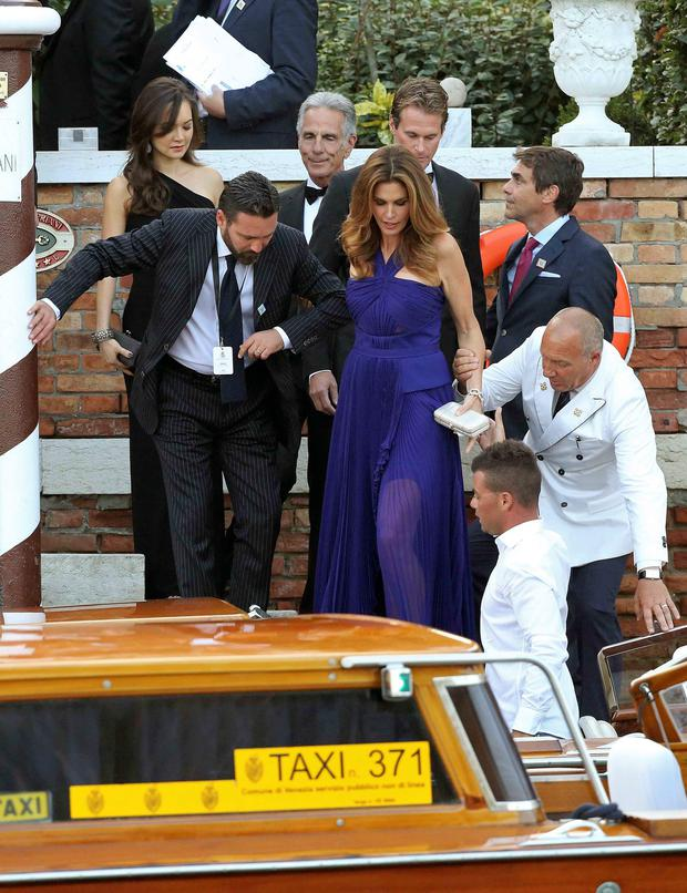 U.S. model Cindy Crawford (C) gets help next to her husband Rande Gerber (back R) as they board a taxi boat transporting guests to the venue of a gala dinner ahead of the official wedding ceremony of U.S. actor George Clooney and his fiancee Amal Alamuddin
