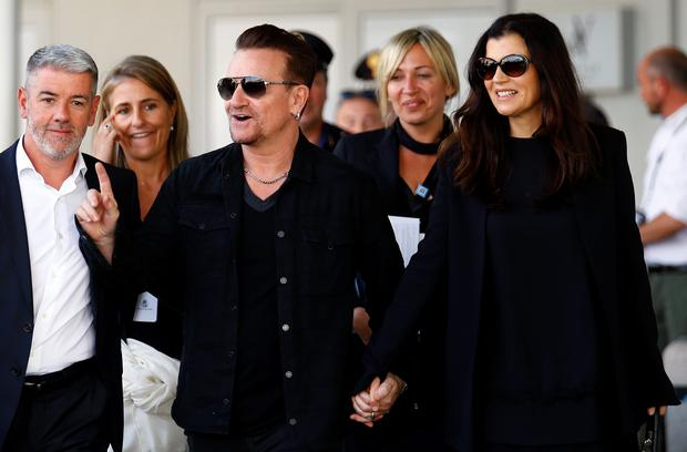 Irish singer Bono, lead singer of group U2, and his wife Ali Hewson arrive to take a taxi boat transporting guests for the wedding of U.S. actor George Clooney