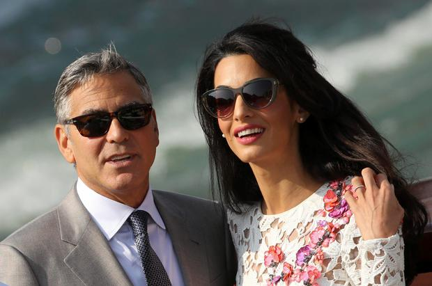 U.S. actor George Clooney and his wife Amal Alamuddin travel on a water taxi at the Grand Canal in Venice September 28, 2014