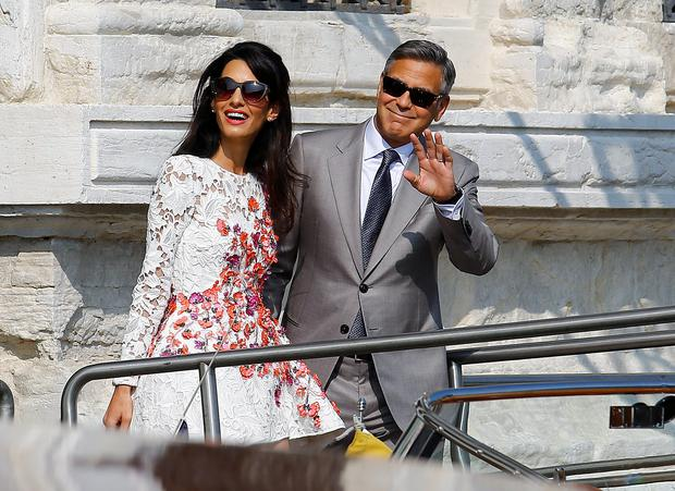 U.S. actor George Clooney and his wife Amal Alamuddin leave the seven-star hotel Aman Canal Grande Venice