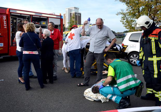Paramedics attend to the wounded at a monster truck festival in Haaksbergen September 28, 2014. Three people were killed, including a child, when a giant pick-up truck spun out of control while attempting to perform a stunt demonstration in the Dutch city of Haaksbergen on Sunday, Dutch public television quoted the local mayor as saying