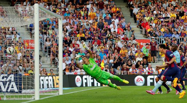 Barcelona's Lionel Messi scores his goal against Granada FC goalkeeper Roberto