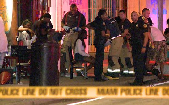 Emergency personnel tend to the wounded outside The Spot in Miami
