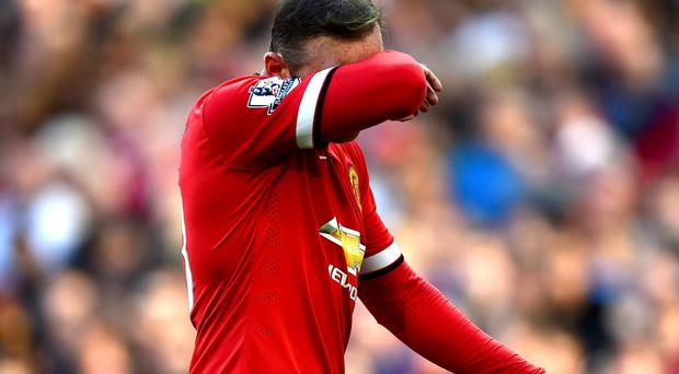 Wayne Rooney of Manchester United walks off the pitch after receiving a red card