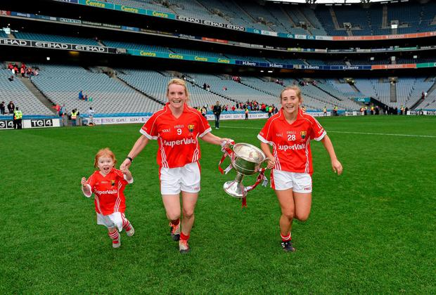 Cork captain Briege Corkery, centre, with her sister Mairead, right, and their niece Bridgín, with the Brendan Martin Cup. Brendan Moran / SPORTSFILE