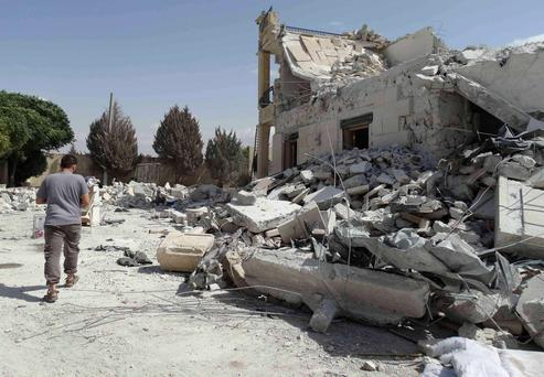 A man walks past damage at a base of the al Qaeda-linked Nusra Front, that was targeted by what activists said were U.S.-led air strikes in Reef al-Mohandeseen al-Thani in Aleppo September 27, 2014. REUTERS/Abdalghne Karoof